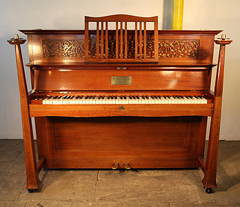 An Arts and Crafts Bechstein  upright piano with a mahogany case, sculptural candlesticks and ornate brass hinges. Designed by Walter Cave