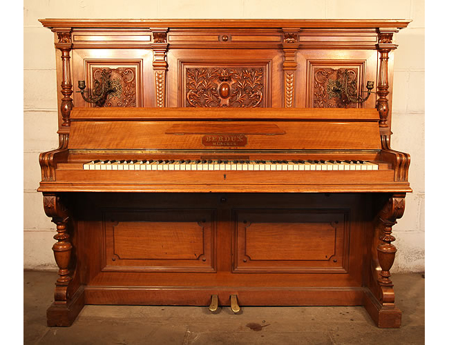 Berdux upright piano with an ornately carved Classical style, mahogany case
