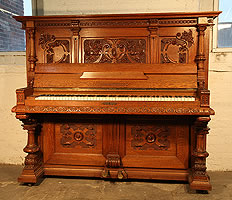 A Bohme upright piano with an ornately carved, classical style, oak case