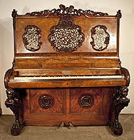 Ernst Rowold Upright Piano For Sale with an Ornately Carved, Black Forest Style Case. Cabinet features  legs carved with sphinx, eagle and ornate fretwork panels with carved floral borders