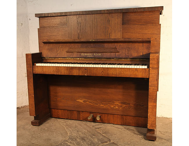 A 1926, Gerhard Adams upright piano with a Modernist almost Brutalist style, oak case. The Brutalist style is seen in the aggressive, arrogant lines and modular planes constucting the piano cabinet