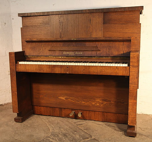 Gerhard Adams upright piano with a Modernist almost Brutalist style, oak case. The Brutalist style is seen in the aggressive, arrogant lines and modular planes constucting the piano cabinet. There is a simplification of form and absence of decoration.