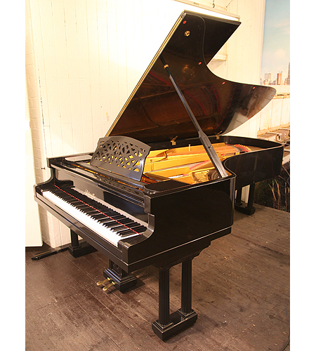A 1922, Ritmuller concert grand piano with a black case and Doric style, fluted column legs