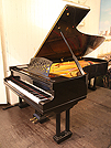 Piano for sale. A Ritmuller Concert grand piano with a black case and Doric style, Fluted column legs.