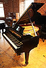 A 1938, Steinway Model S baby grand piano with a black case and spade legs.