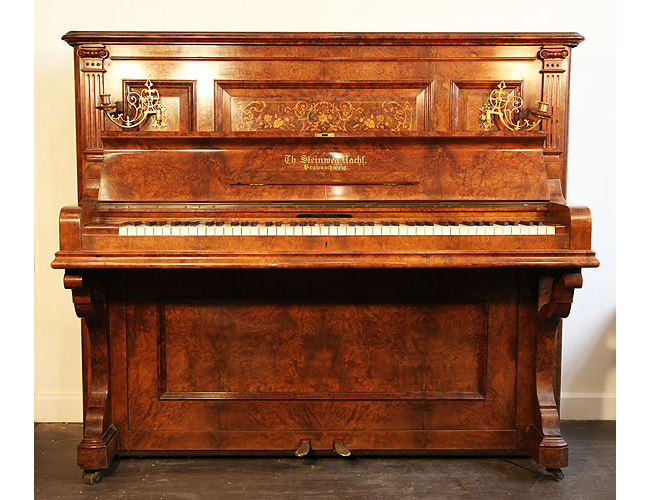 An  1894, Steinweg Nachf upright piano with a burr walnut case and floral inlaid panel. Cabinet features ornate brass candlesticks