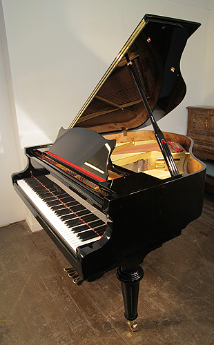A brand new, Besbrode Model 166 Professional grand piano with a black case and turned legs. Piano has three pedals and eighty-eight notes