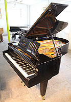 A 1935, Bosendorfer grand piano for sale with a black case, slatted music desk and square, tapered legs