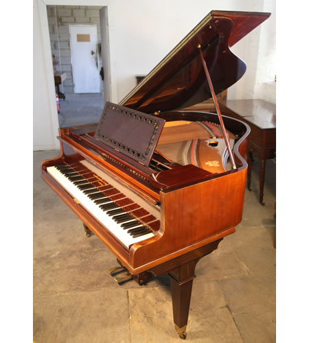 An antique, Broadwood baby grand piano with a polished, rosewood case