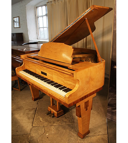 A 1935, Art Deco style, Monington and Weston baby grand piano with a satinwood case and rosewood accents. Piano Legs and music desk feature strong geometric styling