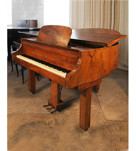 An Art Deco style Strohmenger baby grand piano with a walnut case