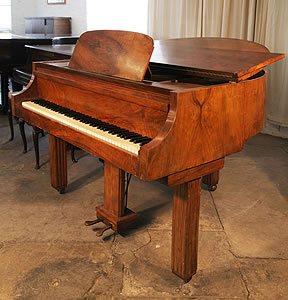 An Art Deco style Strohmenger baby grand piano with a walnut case. Piano Legs amd lyre feature strong geometric styling