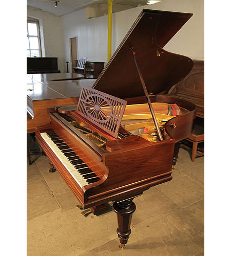 An antique, Bechstein Model A grand piano with a polished, rosewood case and turned legs