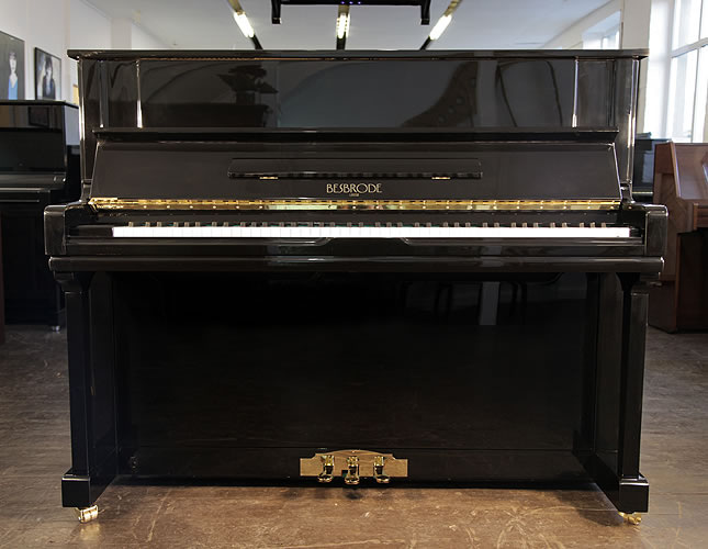 A brand new Besbrode 122 upright piano with a black case and brass fittings