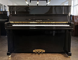 A Brand New Besbrode 122 upright piano with a black case. Piano has an eighty-eight note keyboard and three pedals.