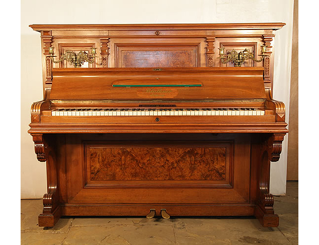 An 1899, Bluthner upright piano with a walnut case. Cabinet features burr walnut panels, ornately carved pilasters and brass candlesticks