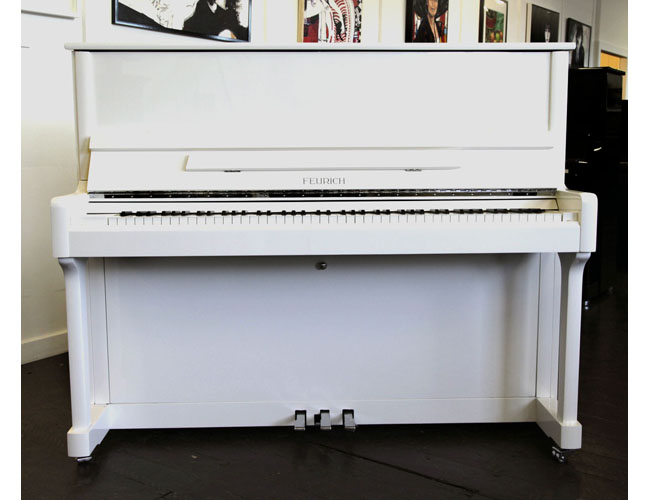 A Brand New Feurich Model 122 upright piano with a white case and chrome fittings