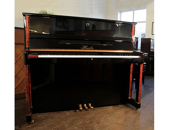 A Haessler upright piano with a black case and faux burr walnut detail