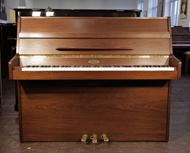 A Kemble upright piano with an American walnut case