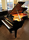 A 1928, Steinway Model O grand piano with a black case and spade legs