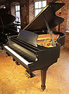 A 1995, Steinway Model L baby grand piano with a satin, black case and spade legs.