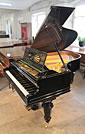 A restored, 1899, Bechstein Model A grand piano with a black case and turned legs