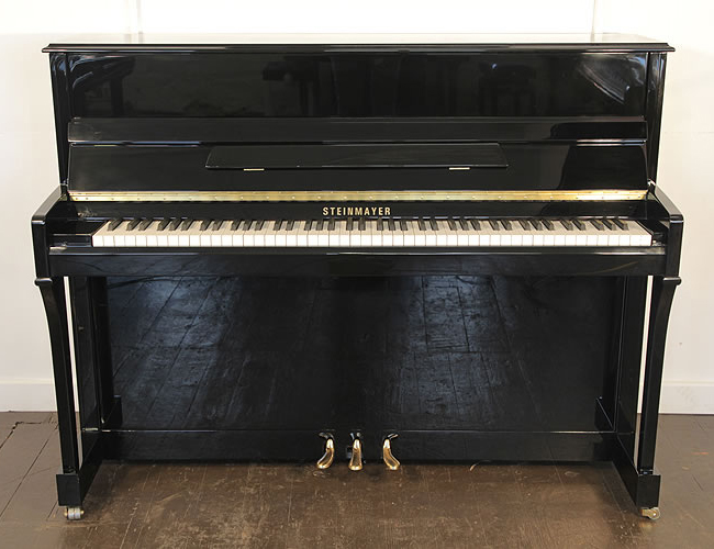 A Steinmayer upright piano with a black case and brass fittings