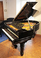 A 1900, Steinway Model A grand piano with a black case and turned, fluted legs.