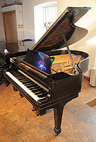 A 1922, Steinway Model O grand piano with a black case and spade legs