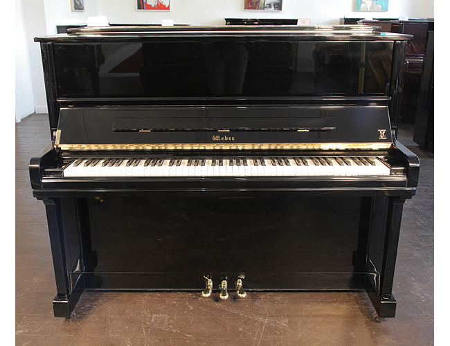 A  Weber W-121 upright piano with a black case and brass fittings