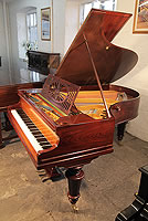 A restored, Bechstein Model A grand piano with a polished, rosewood case and turned legs.