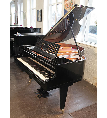 A 1936, Bosendorfer baby grand piano with a black case, slatted music desk and square, tapered legs