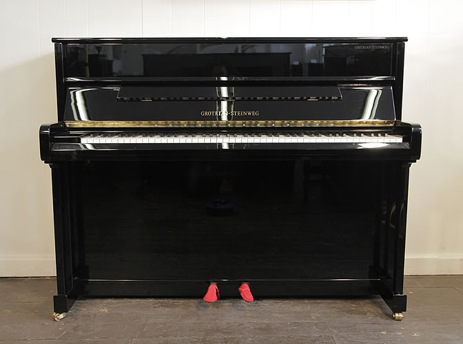 A 2006, Grotrian-Steinweg upright piano with a black case and polyester finish