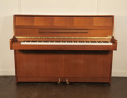 A 1987, Kawai CX-4S upright piano with a polished, mahogany case and brass fittings.