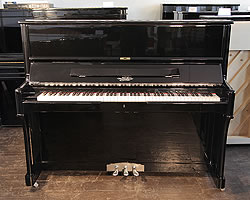 A Moutrie upright piano with a black case and chrome fittings