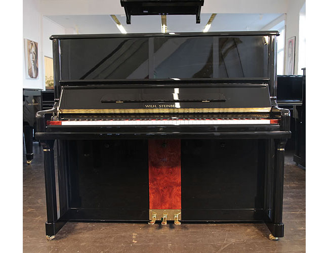 A Brand  New Steinberg Model AT-32 upright piano with a black case and walnut panel