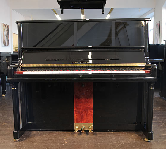 A Brand New Steinberg Model AT-32 upright piano with a black case, walnut panel and brass fittings
