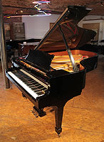 A 2006, Steinway Model B grand piano with a black case and spade legs.