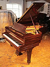 A restored, 1925, Steinway Model B grand piano with a fiddleback mahogany case and spade legs.
