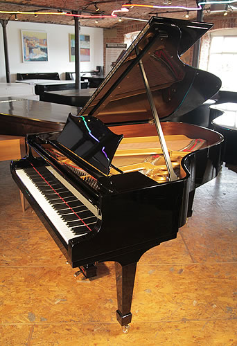A 1929, Steinway Model O grand piano with a black case and spade legs. Piano has eighty-eight notes and two pedals