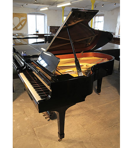 A 1986, Yamaha C5 grand piano with a black case and spade legs.
