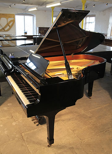 A 1986, Yamaha C5 grand piano with a black case and spade legs
