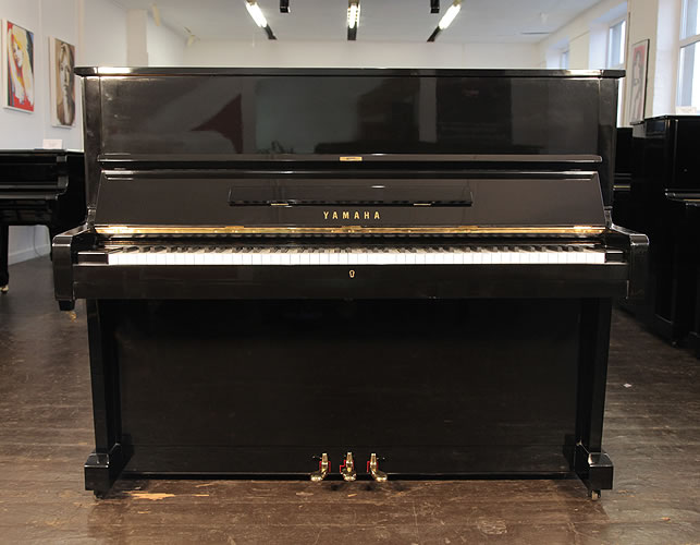 A 1970, Yamaha U1 upright piano with a black case and polyester finish