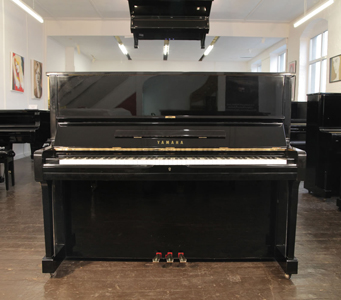 A 1975, Yamaha U1 upright piano with a black case and brass fittings