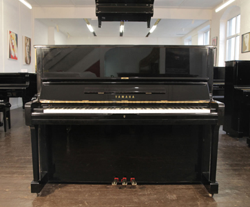 A 1978, Yamaha U1 upright piano with a black case and brass fittings