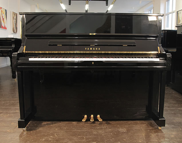 A 2011, Yamaha U1 upright piano with a black case and polyester finish