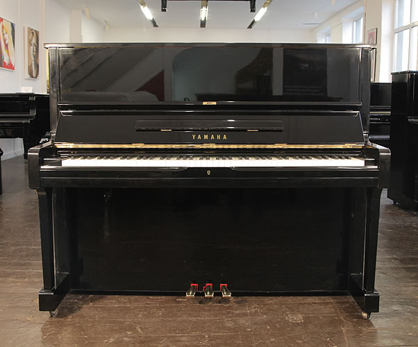 A 1983, Yamaha U1 upright piano with a black case and polyester finish