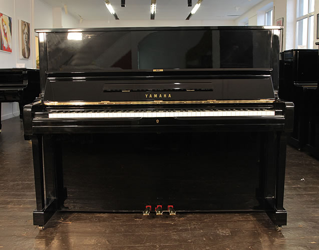 A 1984, Yamaha U1 upright piano with a black case and polyester finish