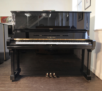 A 1971, Yamaha U3 upright piano with a black case and brass fittings