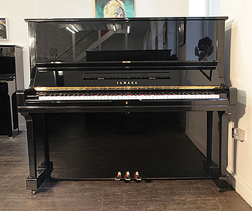 A 1978, Yamaha U3 upright piano with a black case and brass fittings